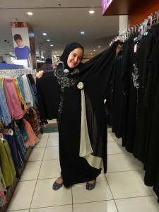 Wearing hijab, carrying an abaya.